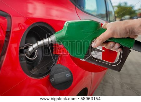 Male hand refilling automobile fuel