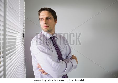 Serious young businessman peeking through blinds in the office