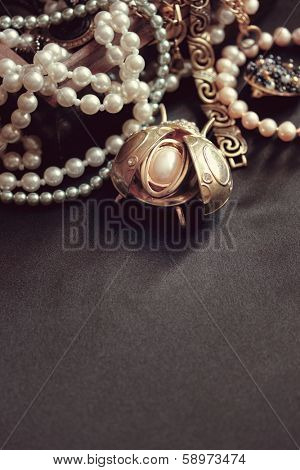 art vintage golden and pearl bijouterie with scarab on black silk background in sepia and peach; vertical card