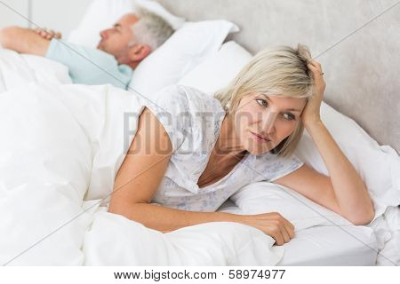 Close-up of a tensed woman lying besides man in bed at home