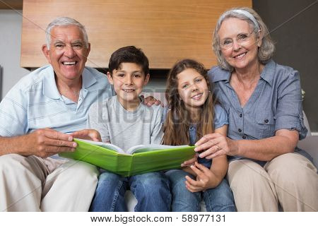 Portrait of happy grandparents and grandkids looking at album photo in the living room