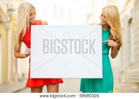 summer holidays, , travel, tourism and advertisement concept - two happy blonde women with blank white board in the city