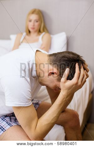 hotel, travel, relationships, and sexual problems concept - upset man sitting on the bed with woman on the back