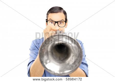 Young male musician blowing into a trumpet isolated on white background
