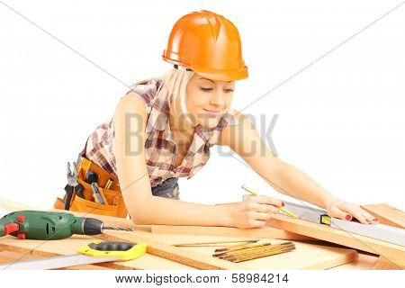 Blond female carpenter measuring a batten isolated on white background
