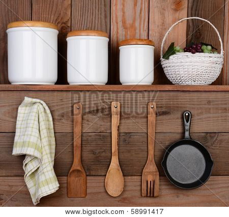 Closeup of a rustic kitchen wall. One shelf with canisters and a basket. Hanging on the wall below are wooden utensils, frying pan and towel.