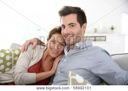 Sweet couple relaxing in sofa at home
