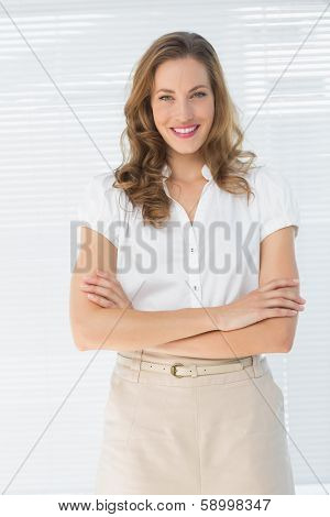 Portrait of a smiling young businesswoman standing with arms crossed against blinds in office