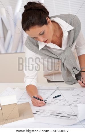 Female Architect Watching Plans At The Office