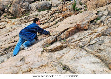 Young Man Climbing Treacherous Steep Mountain Cliff
