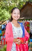 SIEM REAP, CAMBODIA - NOV 21, 2013: A smiling Cambodian woman sitting in her shop beside a road in t