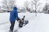 foto of blowers  - Man pushing a gas snow blower on the sidewalk - JPG