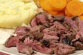 "picture of flank steak  - ""London broil"" marinaded flank of beef steak grilled and sliced thinly, then served with mashed potato, boiled sliced carrots and horseradish sauce, close-up side view - JPG"