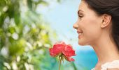 nature and beauty concept - smiling woman smelling flower - smiling woman smelling flower