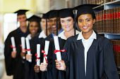 stock photo of graduation gown  - group of happy graduates holding diploma in library - JPG