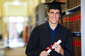 stock photo of laws-of-attraction  - handsome male graduate wearing graduation gown in library - JPG