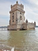 The famous Tower of Belem in the water of the river Tagus. White marble tower is decorated with turr