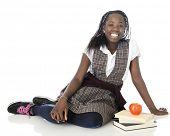 image of tween  - A happy tween girl relaxing on the floor in her school uniform - JPG