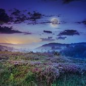 stock photo of moon-flower  - cold morning fog with red hot sunrise in the mountains in moon light - JPG