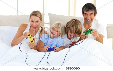 Adorable Family Playing Video Game In The Bedroom