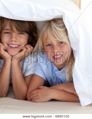 Smiling Siblings Playing Undercovers