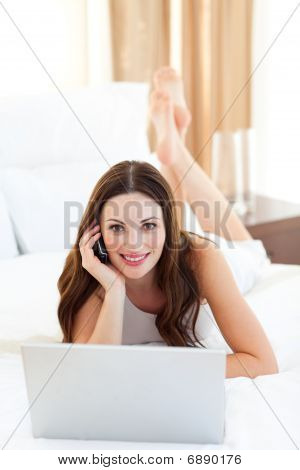 Beautiful Woman On Phone Using Her Laptop Lying On Bed