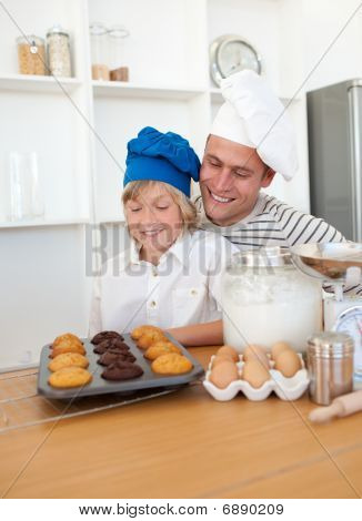 Charming Father And His Son Presenting Their Muffins