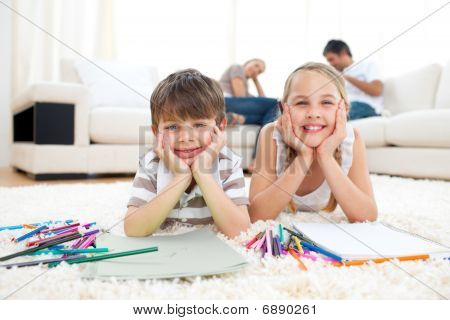 Merry Siblings Drawing Lying On The Floor