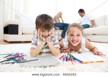 Hermanos sonrientes dibujo tendido en el suelo