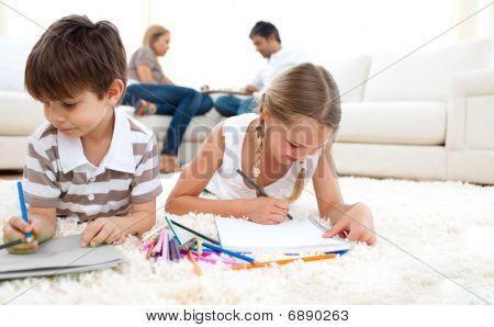 Cute Siblings Drawing Lying On The Floor