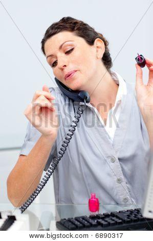 Mujer locuaz en teléfono, pintura de uñas