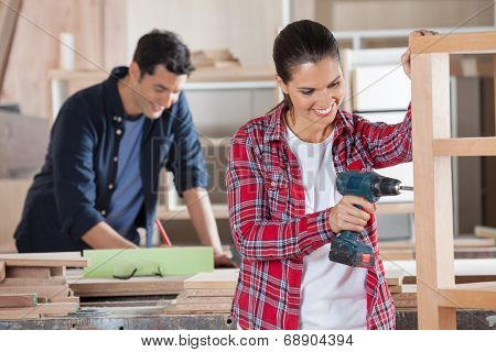Happy female carpenter drilling wood while colleague working in background at workshop