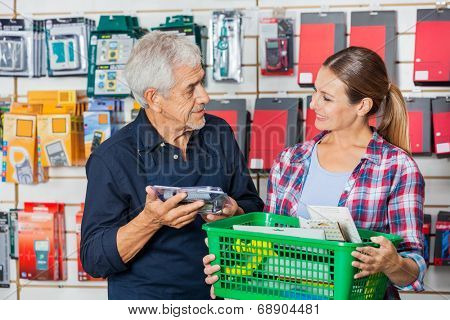 Happy senior worker with female customer holding tools in hardware shop