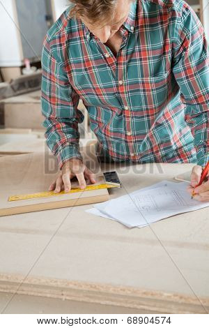 Mid adult carpenter working on blueprint while measuring wood in workshop