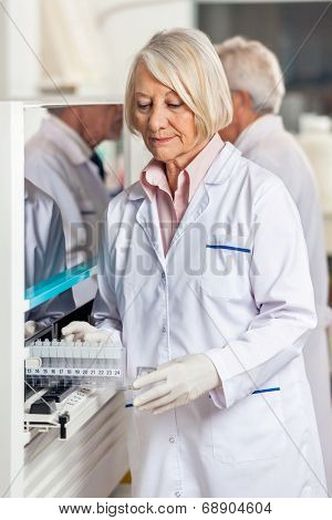 Senior female researcher loading samples in analyzer at laboratory