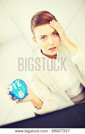 business and time management concept - stressed businesswoman holding clock