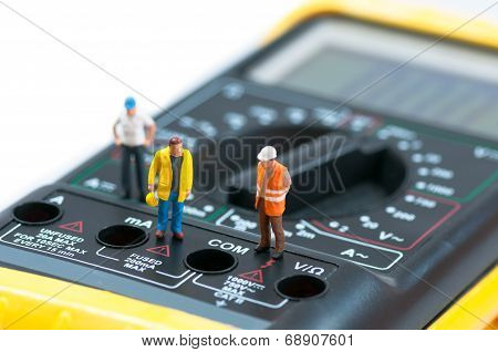 Miniature Workers On Top Of Multimeter