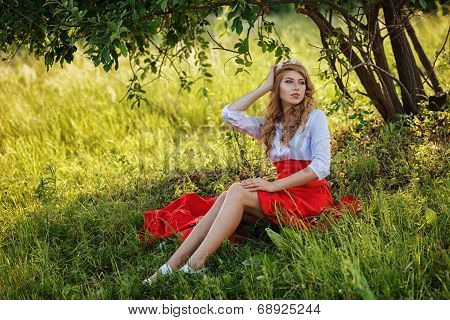 woman wearing skirt sitting under the tree