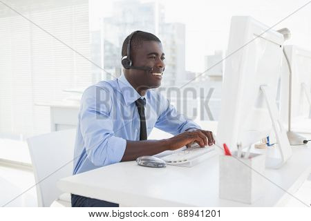 Happy businessman working at his desk wearing headset in his office