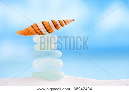 bright stripped sea shell with sea glass ocean , beach and seascape, shallow dof