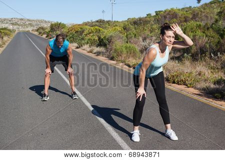 Athletic couple taking a break from jogging on the open road on a sunny day