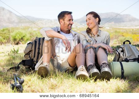 Happy hiking couple taking a break on mountain trail on a sunny day