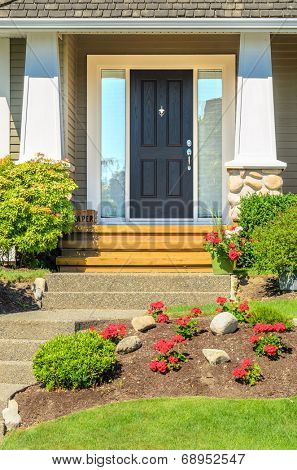A very clean entrance of a house with a nice lawn and outdoor landscape