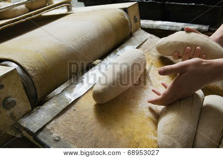 Closeup of baker preparing bread dough at commercial bakery