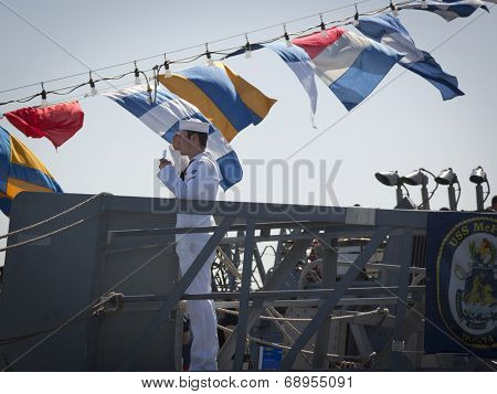 STATEN ISLAND, NY - MAY 25, 2014: A U.S. Navy sailor stops to salute and present his I.D. card on the guided-missile destroyer USS McFaul (DDG 074) moored at Sullivans Piers for Fleet Week NY.