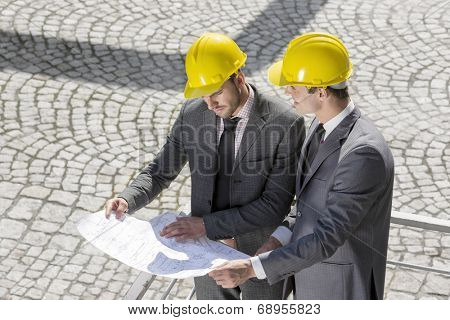 Young male architects analyzing blueprint at construction site