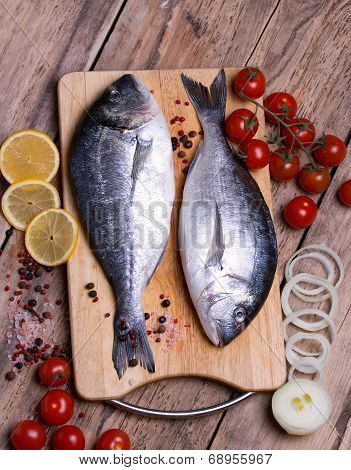 Two fresh gilt-head bream fish on cutting board with lemon,onion and cherry tomato