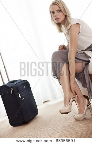 Full length portrait of young businesswoman taking off her shoes in hotel room