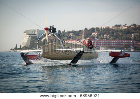 Portoroz, Slovenia - 6 May, 2014: Men riding a motorised vessel on foils in the sea.