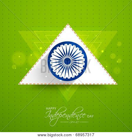 Asoka Wheel with white and saffron color triangle on shiny green background for Indian Independence Day celebrations.
